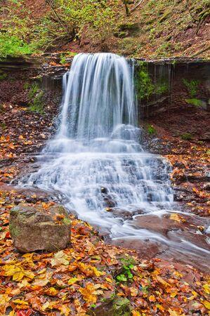 Beautiful waterfall on a mountain stream in the woods Фото со стока