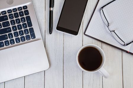 Cup of coffee on white desktop with laptop, notebook, smartphone, pen and glasses. Business concept