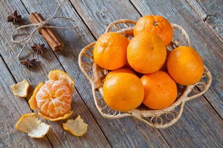 Fresh organic tangerines in a wicker plate on a wooden table