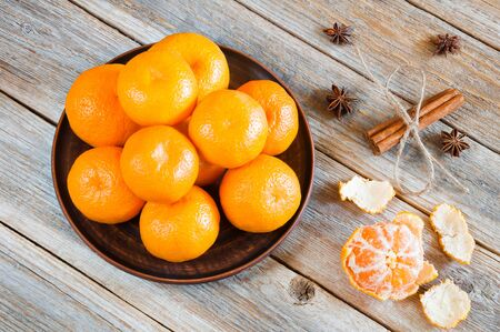 Fresh tangerines in a plate on a wooden table