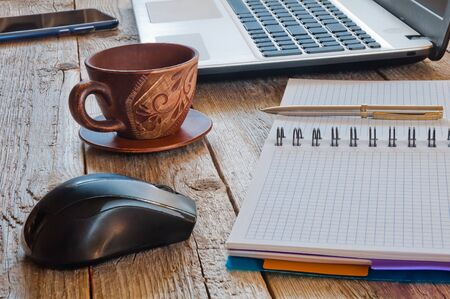 Cup of coffee, laptop, smartphone and notebook with pen on wooden table