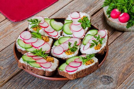 Sandwiches with cheese, cucumbers, radishes and greens on a plate on a wooden table
