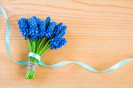 Beautiful bouquet of blue spring muscari flowers on a wooden background Stock Photo