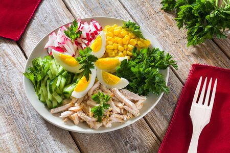 Chicken meat salad with sliced cucumbers and radishes, corn, eggs and greens