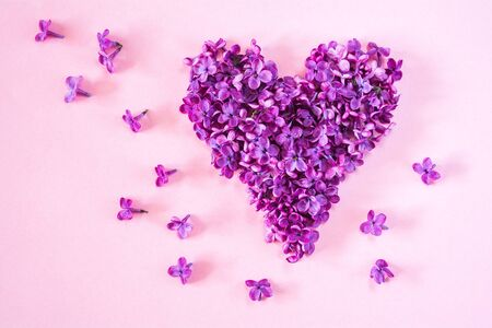 Heart of purple lilac flowers petals on a pink background