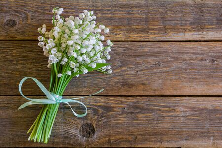 Beautiful bouquet of white lily of the valley flowers on a wooden table
