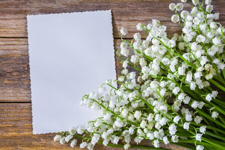 Lily of the valley flowers and greeting card on a wooden table Stock Photo