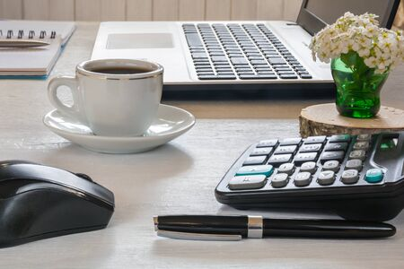 Cup of coffee, laptop with mouse, notebook with pen and calculator on white desktop Stock Photo - 147974624