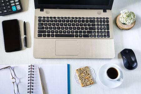 Desktop: laptop, notebook with pen, smartphone, calculator and cup of coffee with cookies Stock Photo