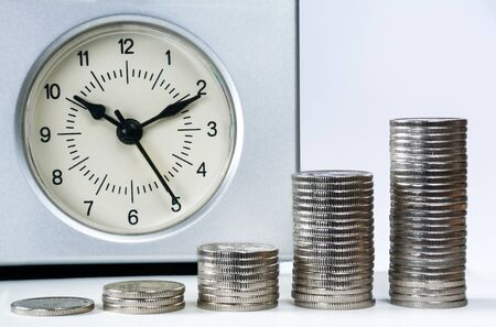 Clock and columns of coins.  Time is money concept Stock Photo - 148106273