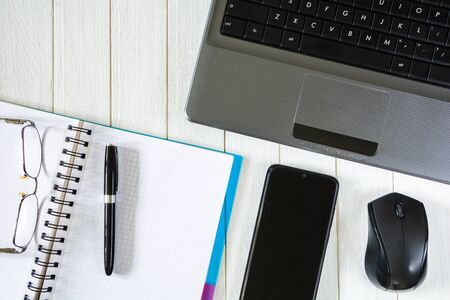 Laptop with mouse, smartphone and notebook with pen and glasses on white desktop Stock Photo