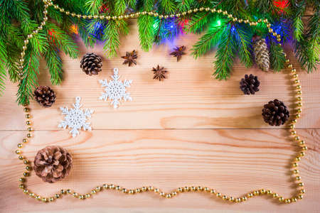 Wooden Christmas background with spruce branches, cones, garlands and decorations
