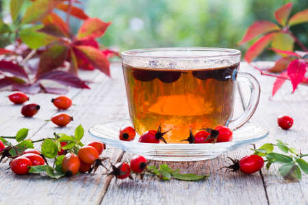 Cup of rose hip tea on a wooden table