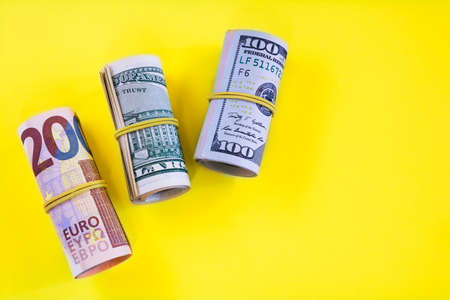 Twisted rolls of dollar and euro banknotes on a yellow background 免版税图像