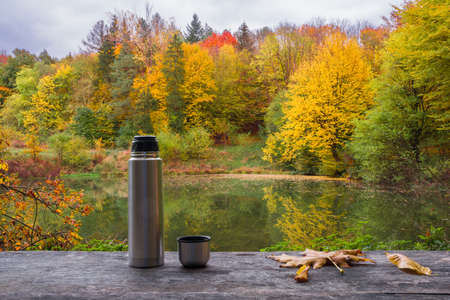 Flask on a wooden table near the lake in the autumn forest. Beautiful autumn landscape