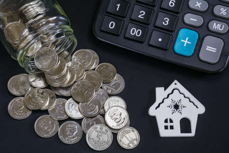 Business concept of finance, savings, mortgage. Model of a house, scattered coins from a glass jar and a calculator on a dark background