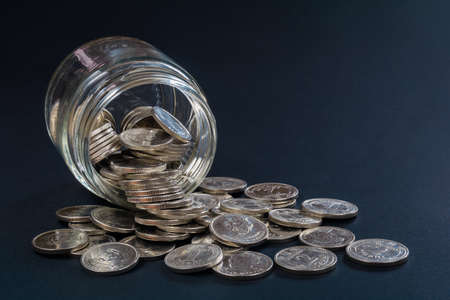 Coins scattered from a glass jar on a dark background