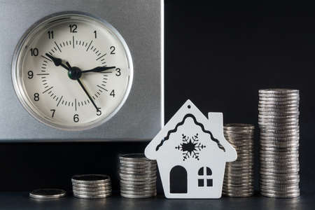 Clock, columns of coins and the contour of the house. Savings concept