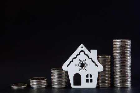 Columns of coins and the contour of the house on a black background. The concept of savings, the concept of profit growth and real estate investment