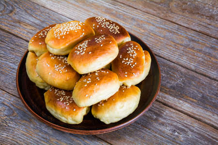 Fresh baked buns sprinkled with sesame seeds in a plate on a wooden table