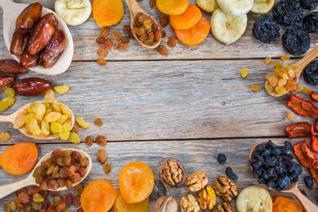 Frame of different dried fruits on a wooden background