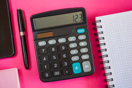 Calculator, notebook and pen on a pink surface