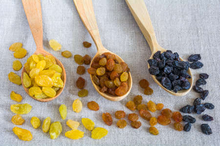 Different types of raisins on wooden spoons on sacking background