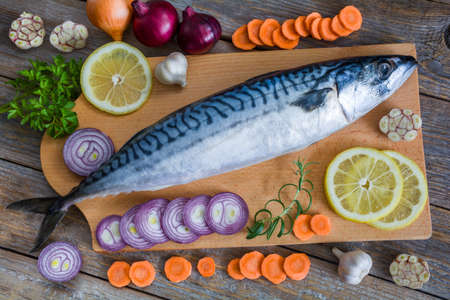 Fresh raw fish mackerel and ingredients for cooking on a wooden background