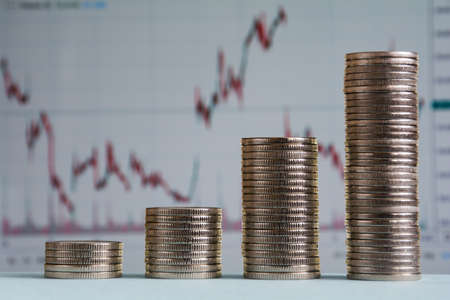 Columns of coins on a background of stock charts. The concept of financial growth