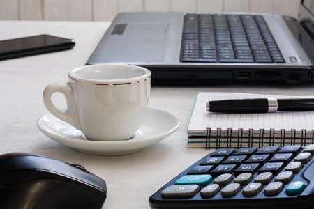 Desktop: laptop, notebook with pen, cup of coffee, calculator and smartphone