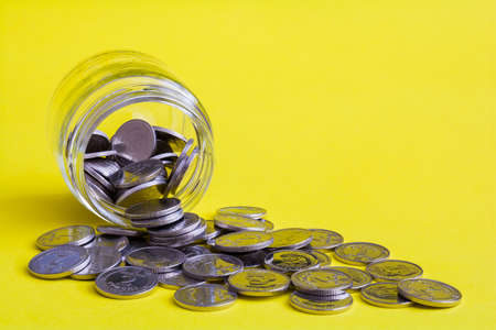 Coins scattered from a glass jar on a yellow background