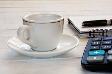 Cup of coffee, notebook with pen and calculator on white desktop