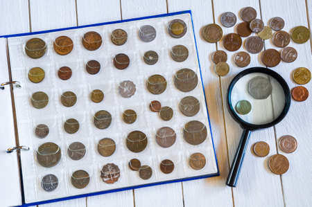 Page of numismatics album with different coins on a white wooden table Stock Photo