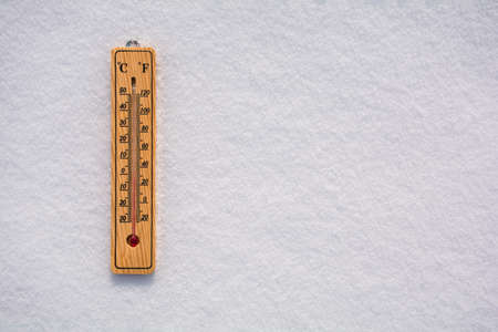 Celsius and Fahrenheit thermometer on the surface of white pure snow. Copy space