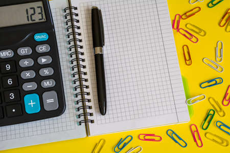 Calculator, notebook and pen on a yellow surface Stock Photo