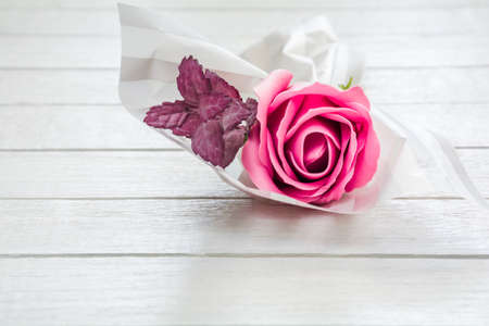 Delicate bouquet of pink roses made of fragrant soap on a white wooden table