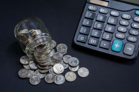Coins scattered with glass jars and calculator on a dark background