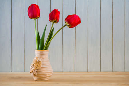 Beautiful bouquet of red tulips in a vase on the table. Still life Stock Photo