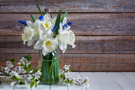 Bouquet of beautiful daffodil flowers in a vase on a wooden table. Still life