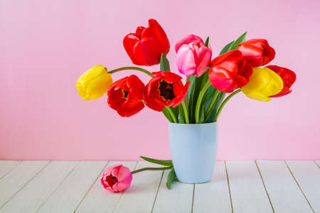 Beautiful bouquet of tulips in a vase on a white wooden table on a pink background