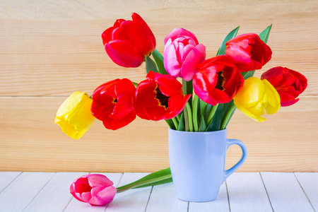 Beautiful bouquet of tulips in a vase on a wooden table