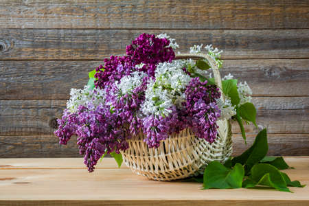 Bouquet of colorful lilac flowers in a wicker basket on a wooden table Stock Photo