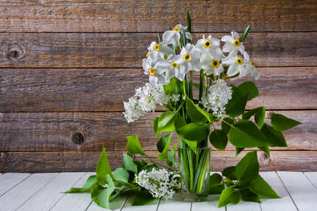 Bouquet of white flowers of daffodils and lilacs in a glass on a wooden table. Still life