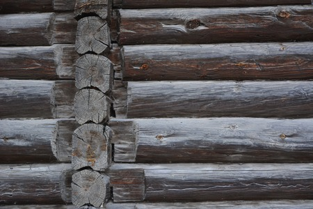 Old wooden wall of blockhouse. Facade of a log house built at the end of 19th century without nails in Russia.