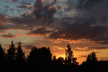 Beautiful sunset sky with dramatic light over the forest. Cloudscape in summer evening.
