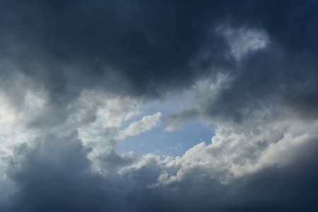 Thunder Sky. Dramatic cloudscape with blue sky in the center, surrounded by gray clouds 版權商用圖片 - 154927108