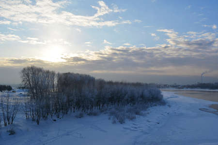 Winter scene with river partially under ice and trees on the bank in the evening 免版税图像