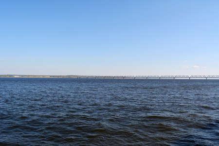 Landscape with bridge over dark blue water of Volga river.