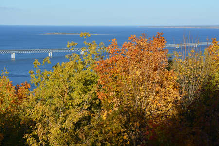 Beautiful autumn landscape in Russia. The bridge over the Volga river and trees with colorful leaves on the foreground. 版權商用圖片