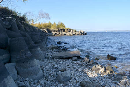 River bank with stones and breakwaters in september.